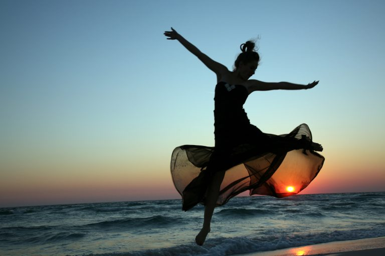 Free Spirit ... Young woman acting carefree as she dances and jumps in the air during sunset at the beach. Lots of copy space!