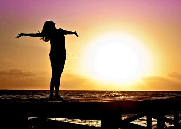thriving woman on pier at sunset