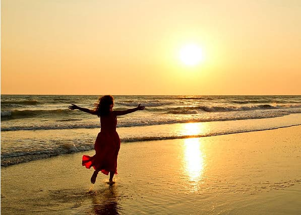 Happy, thriving woman running on a beach at sunset