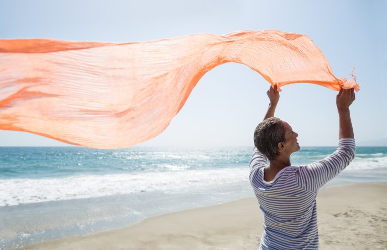 Senior woman standing on beach holding scarf. iStockalypse LA California